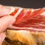 43936927 - caucasian man left hand over serrano ham with slice