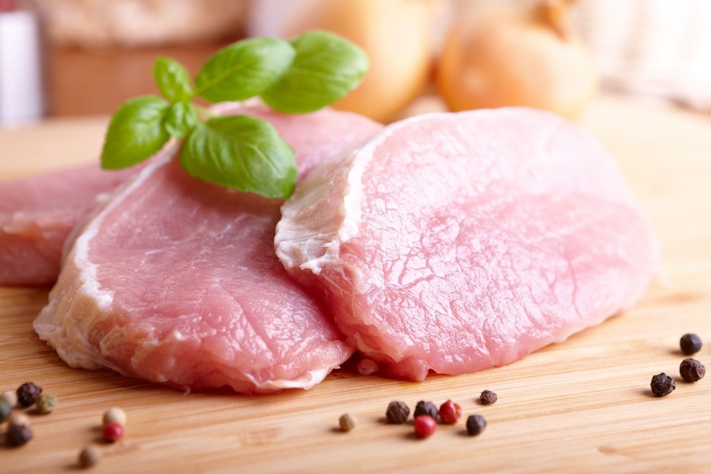 8887410 - fresh raw pork chops on wooden cutting board with  pepper and basil